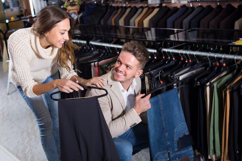 Junge liebevolle Paare, die auf neuer Hose entscheiden stockfotos