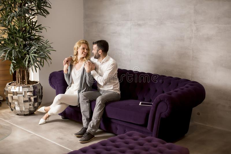 Junge liebevolle Paare, die auf Sofa und lookind auf digitaler Tabelle sitzen stockfoto
