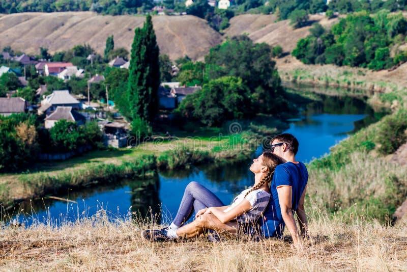 Junge liebevolle Paare, die in der Umarmung auf die Oberseite eines Hügels mit herrlicher Aussicht des Flusses sitzen lizenzfreie stockbilder