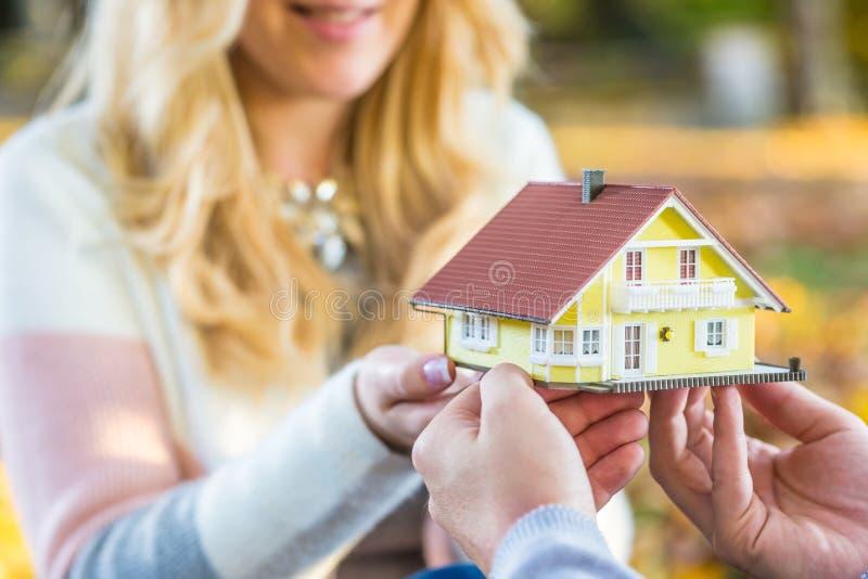 Junge liebevolle Paare, die kleines Musterhaus halten stockfoto