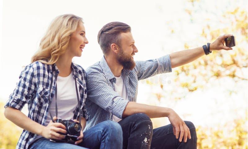 Junge liebevolle Paare, die selfie Foto im Herbstpark machen stockfotografie