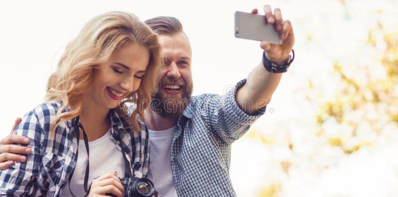 Junge liebevolle Paare, die selfie Foto im Herbstpark machen stockbilder