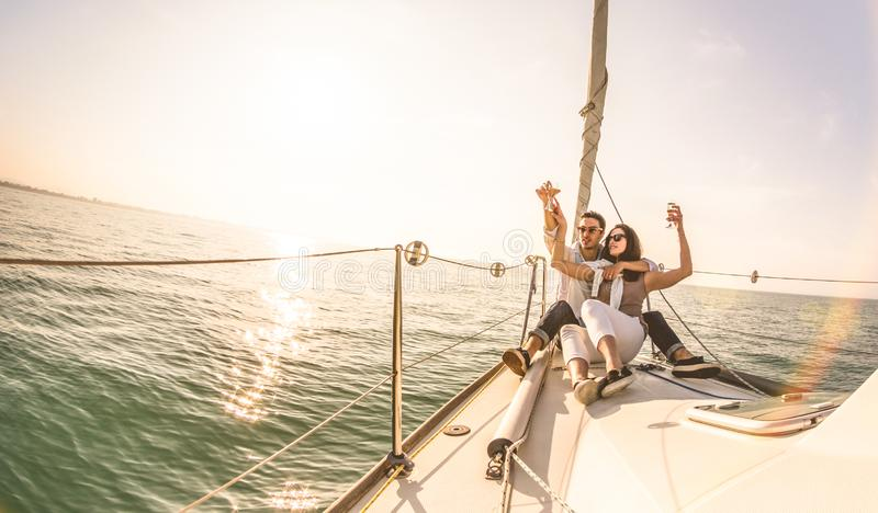 Junge Liebhaberpaare auf Segelboot mit Champagner bei Sonnenuntergang - exklusives Luxuskonzept mit reichem tausendjährigem Leute lizenzfreie stockfotografie