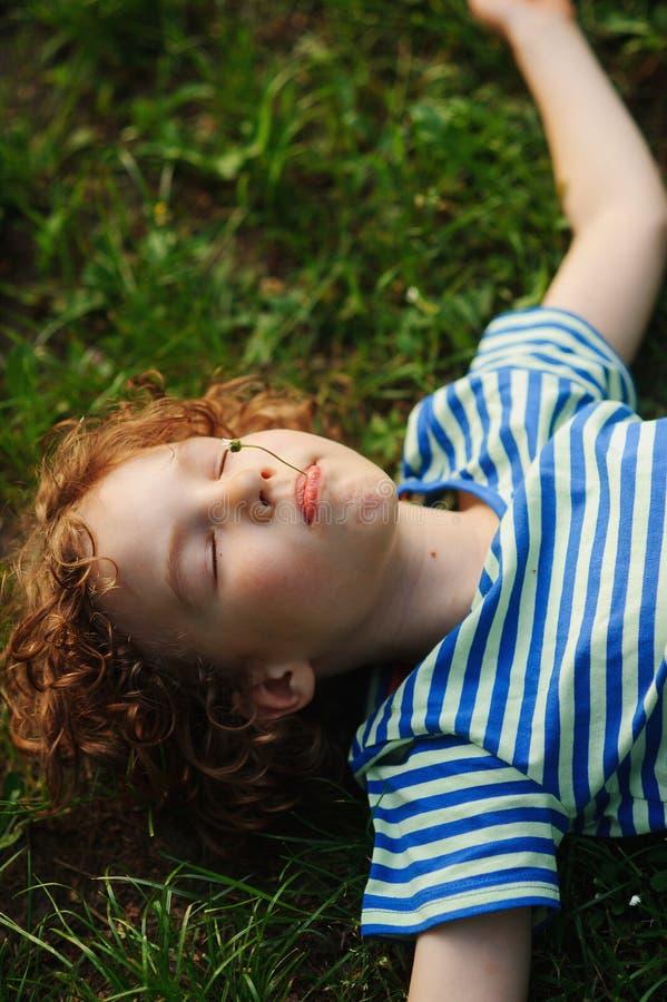 Junge liegt auf der Erde, die Hände in den Parteien ausgedehnt wird lizenzfreie stockfotografie