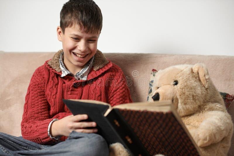 Junge liest ein Buch, sitzt auf dem Sofa mit einem Bärnspielzeug lizenzfreie stockfotos
