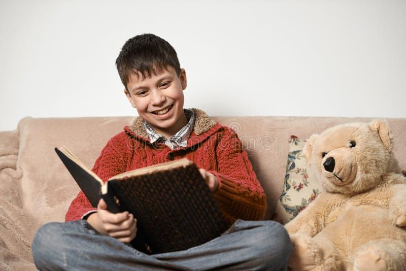 Junge liest ein Buch, sitzt auf dem Sofa mit einem Bärnspielzeug stockfoto