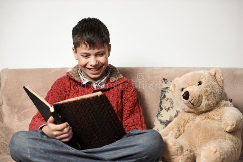 Junge liest ein Buch, sitzt auf dem Sofa mit einem Bärnspielzeug lizenzfreie stockfotografie