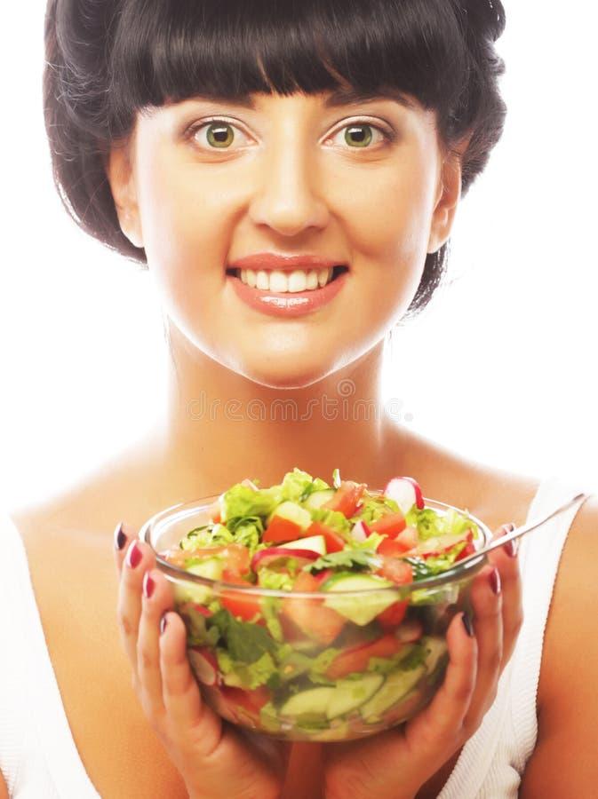 Junge lustige Frau, die Salat isst stockfotos