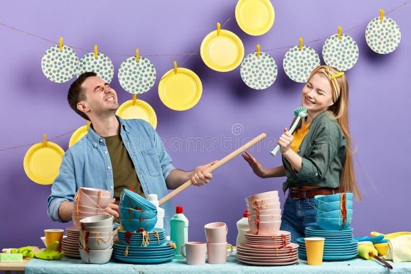 Junge lustige Mann- und Frauen-Gesanglieder und Tanzen mit Reinigungswerkzeugen stockbilder