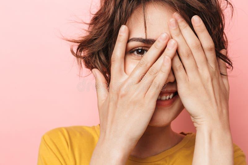 Junge lustige Schönheitsaufstellung lokalisiert über rosa Wandhintergrund-Bedeckungsgesicht lizenzfreies stockfoto