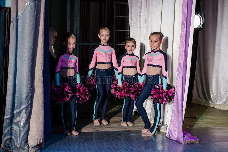 Junge Mädchen - Athleten bereiten sich für die Show, viele jungen Cheerleadern stehen auf Stadium hinter dem Vorhang, Sportler si lizenzfreie stockbilder