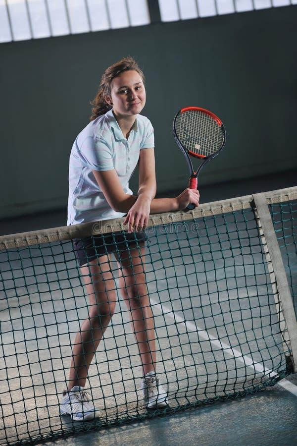 Junge Mädchen, die das Tennisspiel Innen spielen stockfotos