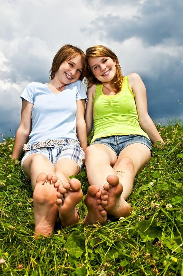 Junge Mädchen, die in der Wiese sitzen lizenzfreie stockfotografie