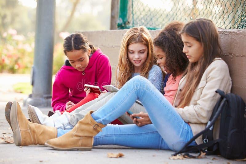 Junge Mädchen, die Digital-Tablets und -Handys im Park verwenden lizenzfreie stockbilder