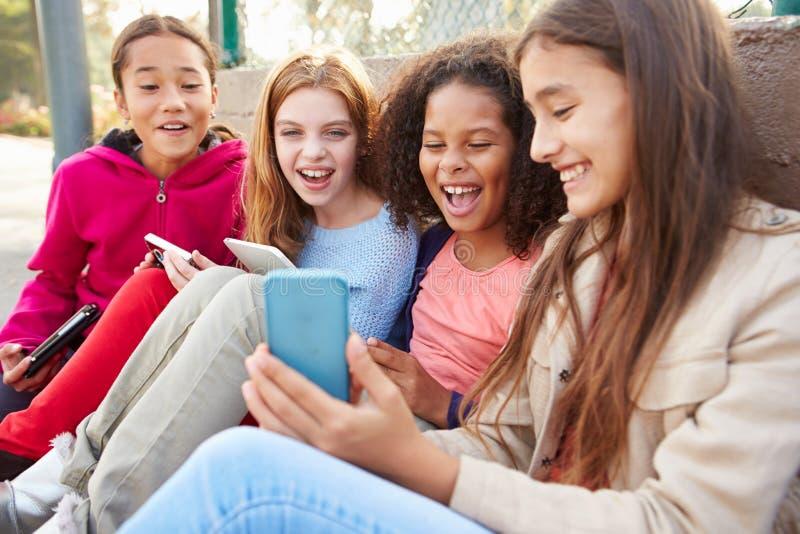 Junge Mädchen, die Digital-Tablets und -Handys im Park verwenden lizenzfreie stockfotos