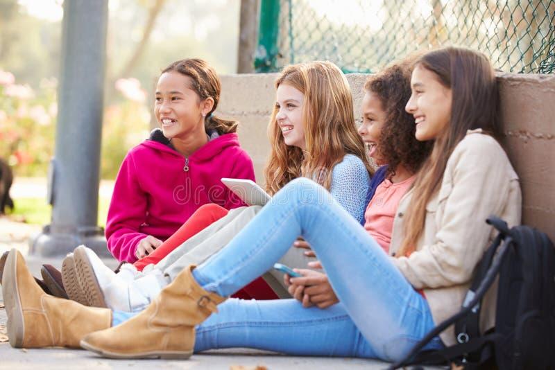 Junge Mädchen, die Digital-Tablets und -Handys im Park verwenden stockfotografie
