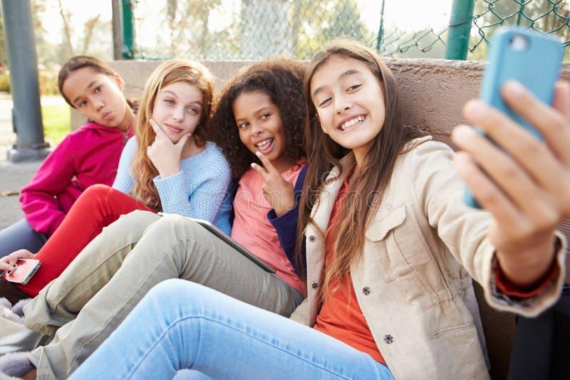 Junge Mädchen, die Selfie mit Handy im Park nehmen stockfotos