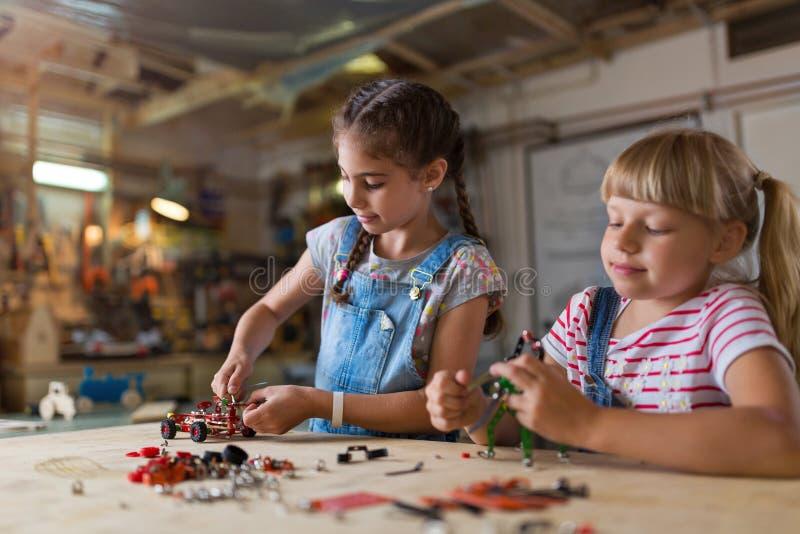 Junge Mädchen, die Spielzeugbaumaschine errichten stockbilder