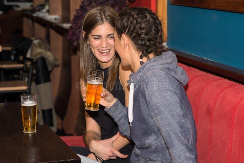 Junge Mädchen, die zusammen Spaß trinken und haben stockbild