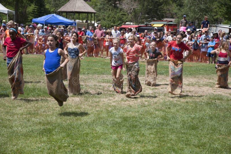 Junge Mädchen konkurrieren in mit Beinen versehenem Rennen drei lizenzfreie stockfotografie