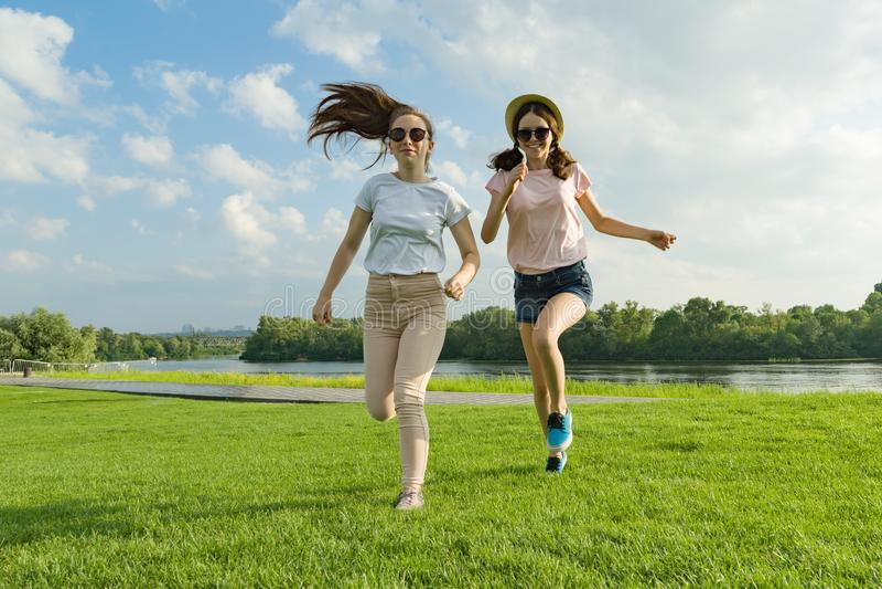 Junge Mädchen laufen Jugendliche, die Spaß auf dem grünen Rasen im Park, sonnigen Sommertag genießend haben lizenzfreie stockfotos
