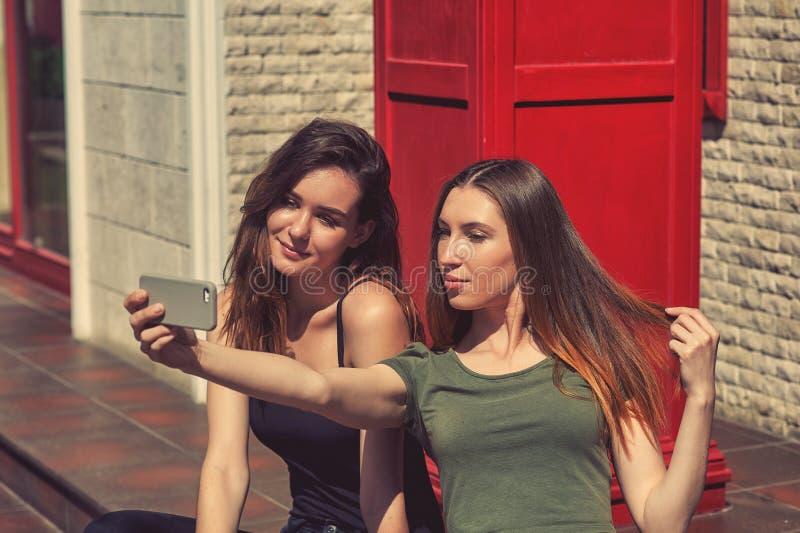 Junge M?dchen nehmen selfies unter Verwendung eines Handys auf der Stra?e der Stadt stockbild