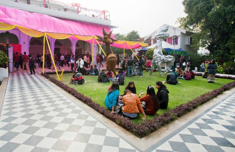 Junge Mädchen und andere Besucher, die auf dem Rasen während des populären Jaipur-Literatur-Festivals sitzen stockbilder