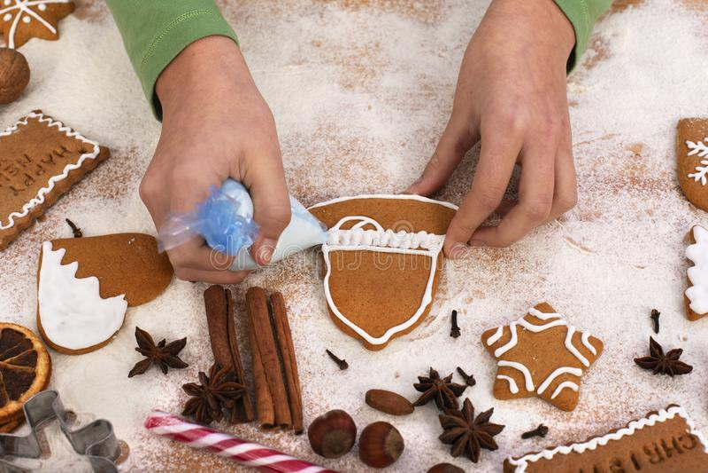Junge Mädchenhände dekorieren Fingerbrettkekse mit weißer Vereisung - Top-Ansicht, Nahaufnahme lizenzfreie stockfotos