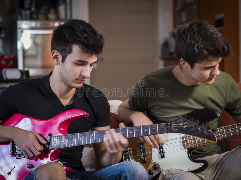 Junge Männer, die E-Gitarren spielen stockfotos