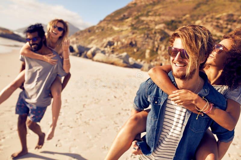 Junge Männer, die Frauen auf dem Seeufer huckepack tragen stockfotos