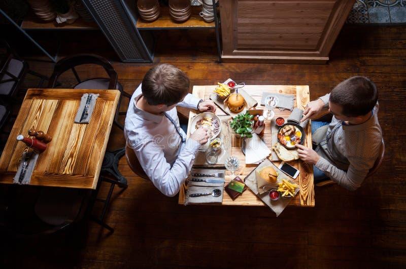 Junge Männer, die heraus im Café essen stockfotografie