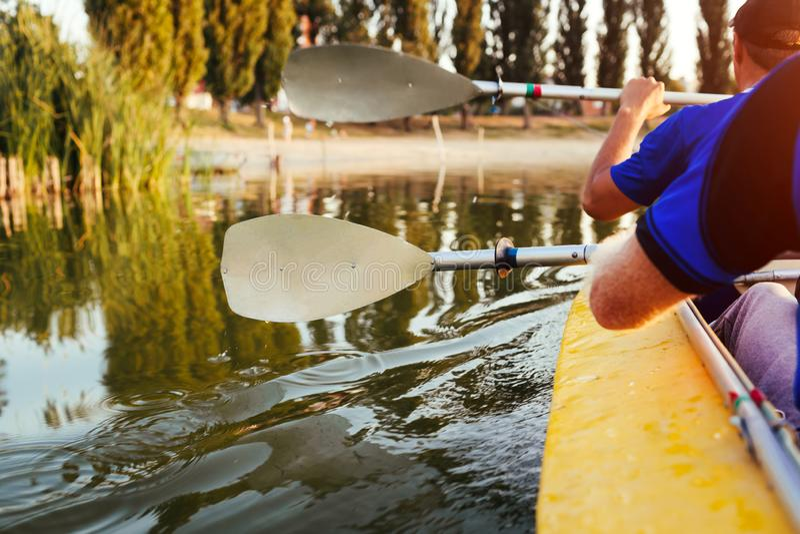 Junge Männer, die Kajak auf Fluss bei Sonnenuntergang rudern Verbinden Sie von den Freunden, die den Spaß haben, der im Sommer ca lizenzfreie stockfotografie