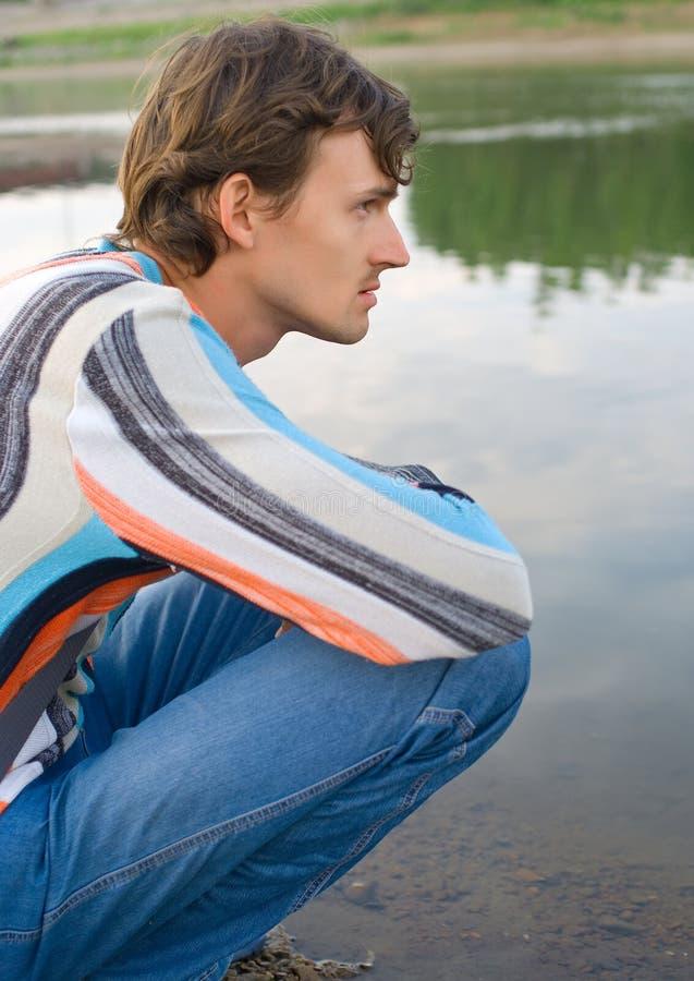 Junge Männer gegen Küste von Fluss lizenzfreies stockbild