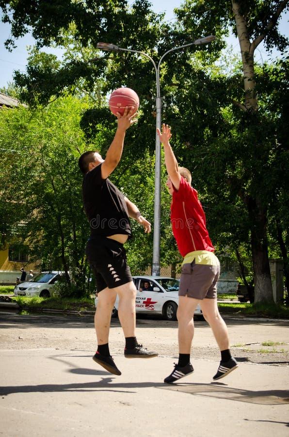 Junge Männer spielen Amateurbasketball im Sommer Tiefpunktschießen stockbild