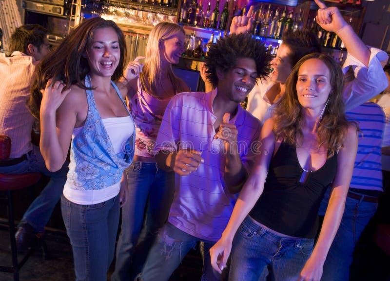 Junge Männer und Frauen, die in einen Nachtklub tanzen stockbild