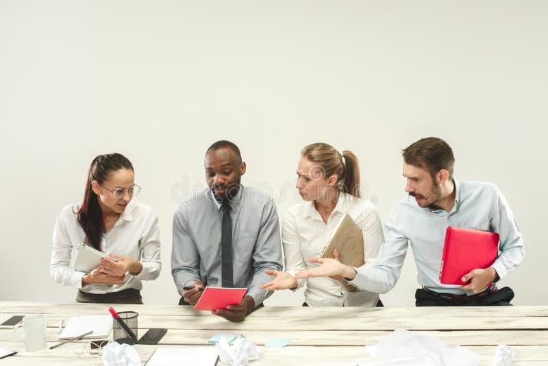 Junge Männer und Frauen, die im Büro sitzen und an Laptops arbeiten Gefühlkonzept stockfotos