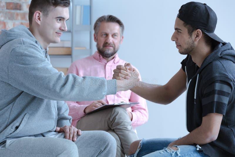 Junge Männer versöhnt während der Therapie mit Ratgeber für rebelliou stockfotografie