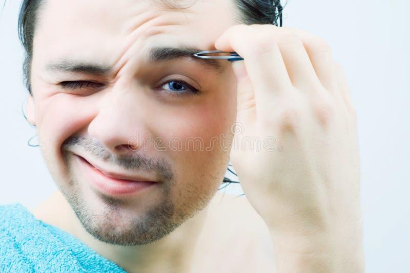 Junge Männer zupfen seine Augenbrauen. lizenzfreie stockfotografie