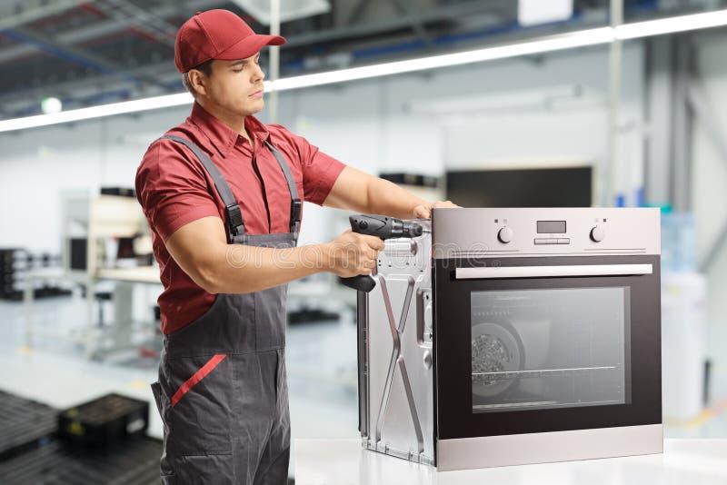 Junge männliche Arbeitskraft, die mit einer Bohrmaschine auf einem elektrischen Ofen arbeitet stockfotografie