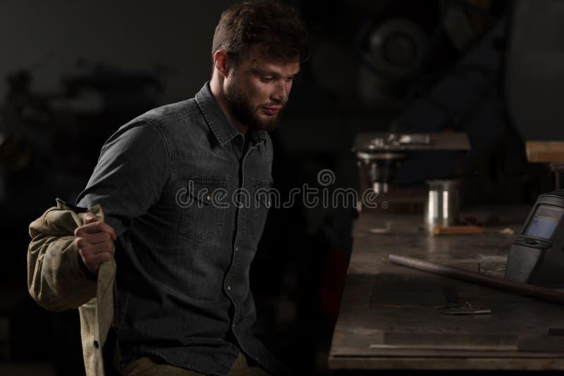 junge männliche Arbeitskraft, die Uniform entfernt und nahe Tabelle sitzt stockfoto