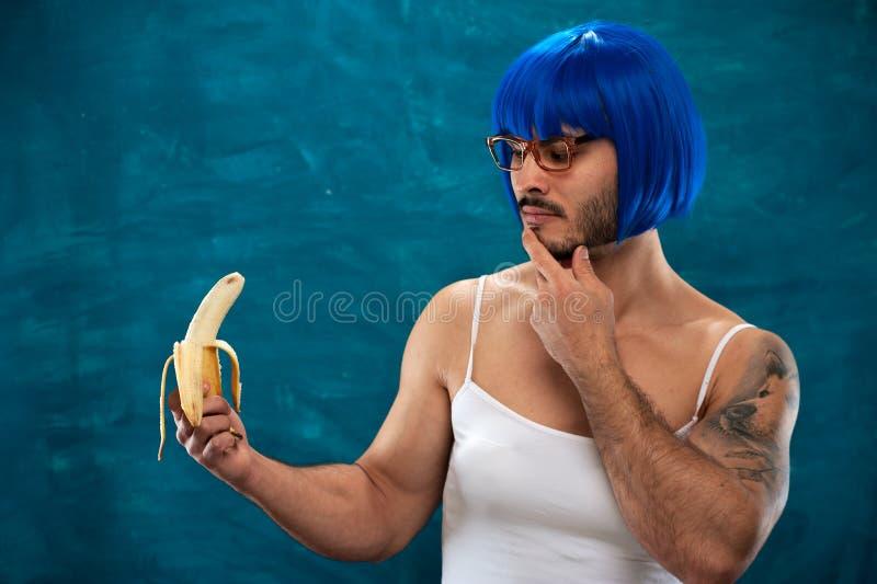 Junge männliche Cross-Dressingperson, die blaue Perücke trägt lizenzfreies stockfoto