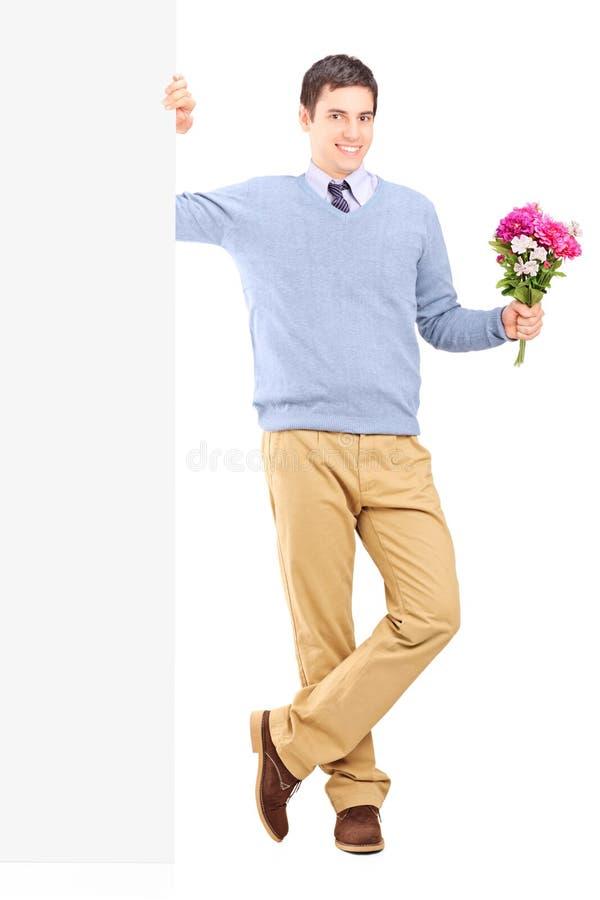 Junge männliche Holdingblumen nahe bei einem Panel lizenzfreie stockfotografie
