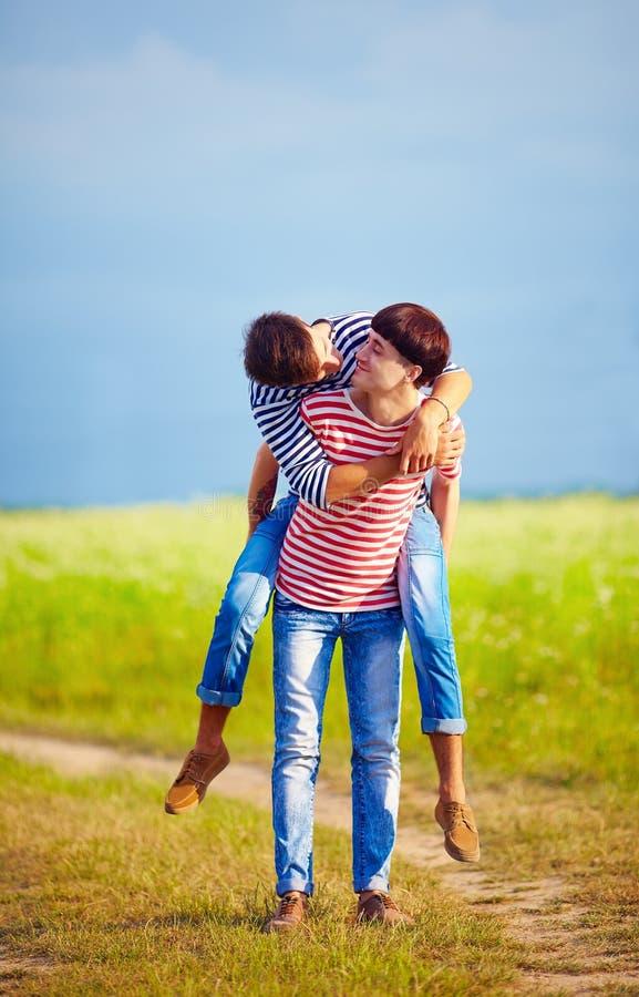 Junge männliche Paare, die Spaß am Frühlingsfeld haben stockfoto
