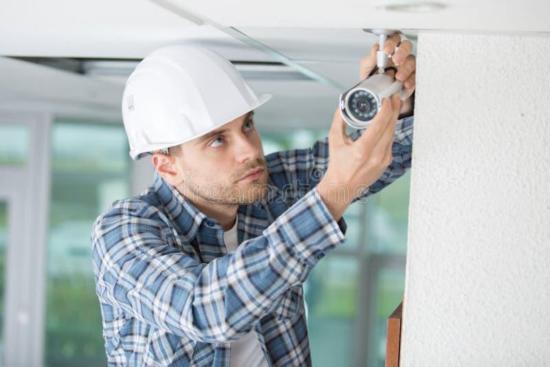 Junge männliche Techniker-Installing Camera On-Wand lizenzfreie stockfotografie