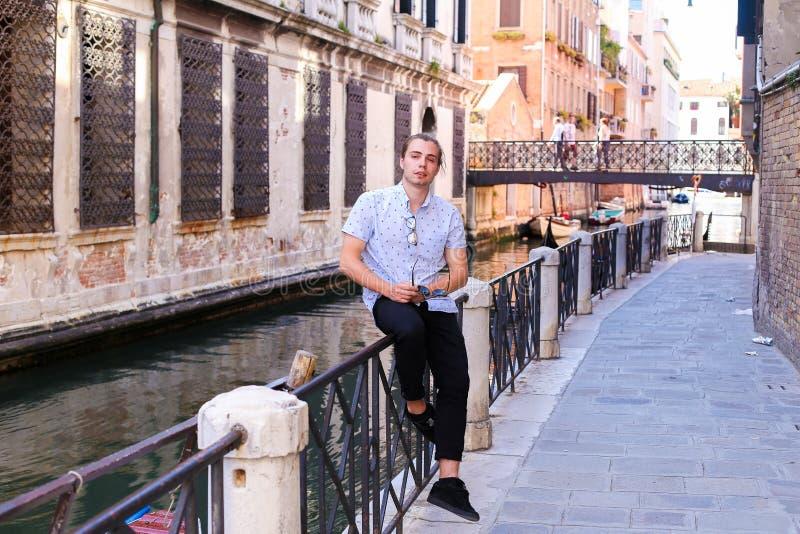 Junge männliche Touristen sitzen auf dem Banister in Venedig, Italien stockbilder
