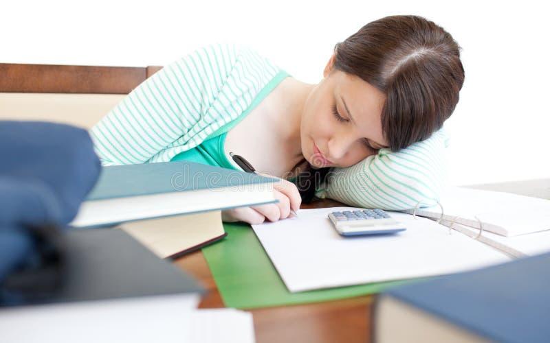 Junge müde Frau, die auf einer Tabelle studiert stockbild