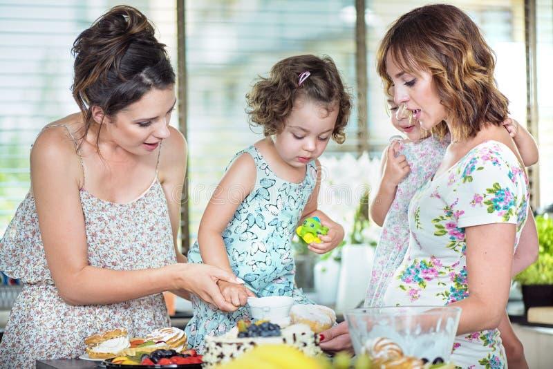 Junge Mütter, die einen Kuchen mit ihren Töchtern machen stockbild