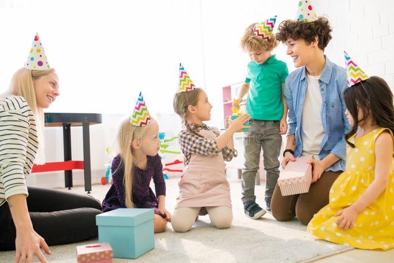 Junge Mütter, die mit Kindern an der Geburtstagsfeier spielen stockfotos