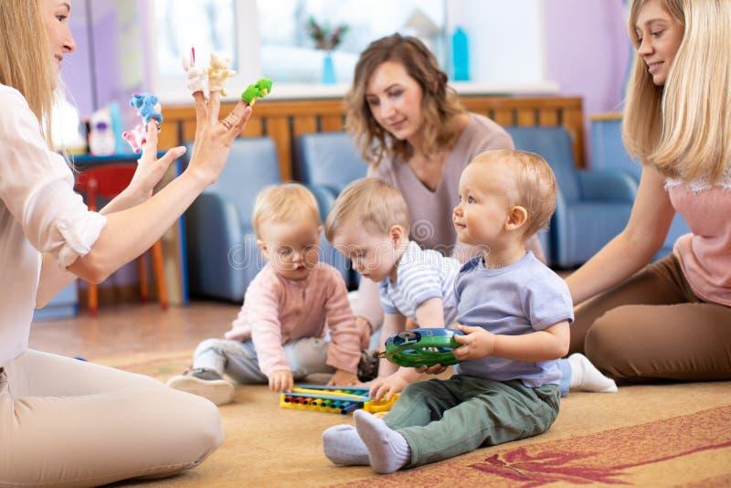Junge Mütter und ihre Kinder zusammen im Verein stockbilder