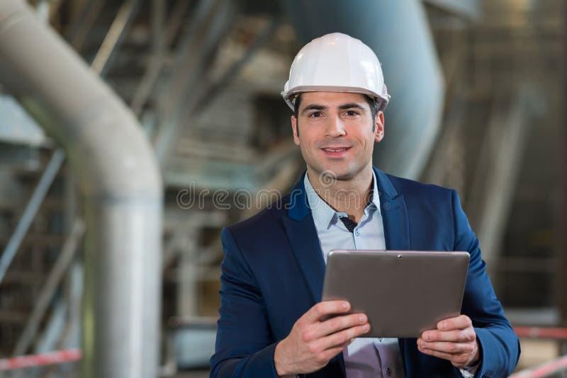 Junge m?nnliche Aufsichtskraft, die Tablet-PC in der Industrie verwendet lizenzfreie stockfotografie